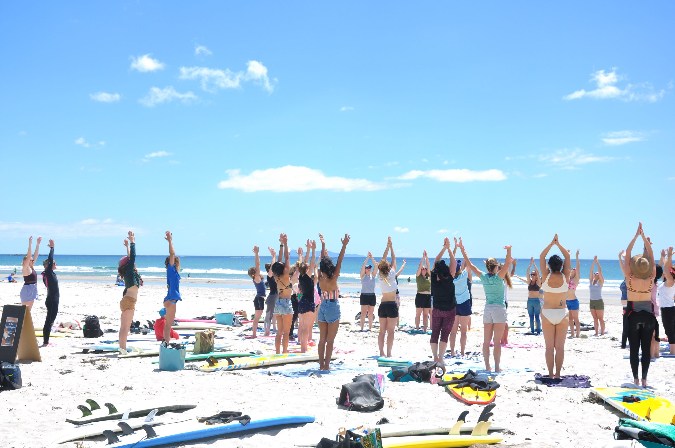 Group of girls all doing yoga together on the beach in Mount Maunganui